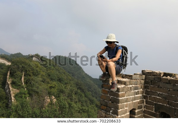 successful woman hiker taking photo with smart phone on top of great wall