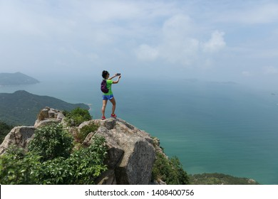 Successful Woman Hiker taking picture with smartphone In Seaside Mountain Top