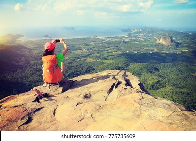 successful woman hiker taking picture with smartphone at cliff edge on mountain top