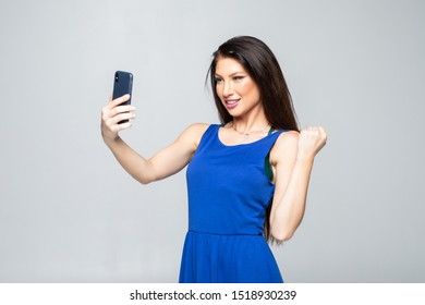 Successful woman holding obile phone isolated on a white background
