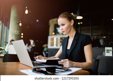 Successful woman jurist using textbook while reading article on web site via laptop computer, sitting in modern restaurant. Confident female marketing specialist checking e-mail via portable netbook