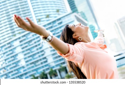 Successful woman with open arms looking very happy