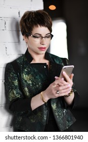 Successful woman professional psycologist or lawer in glasses is reading news or message on her cell phone on background of modern office