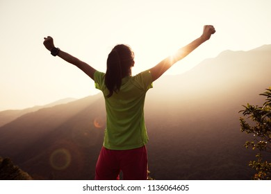 successful woman raised arms to summer sunrise on mountain top