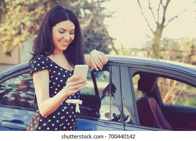 Successful woman standing by her car texting on mobile phone