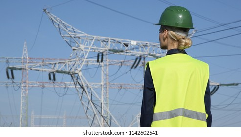 Successful Worker Woman Analyzing Activity and Looking Out at Electricity Pylon Power Wire Lines Network