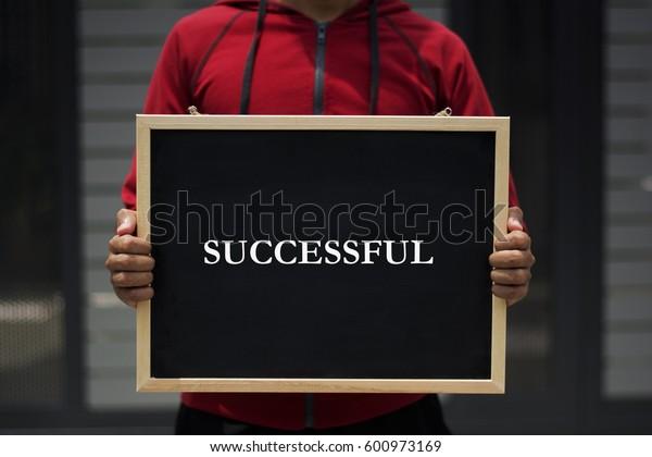 successful written on blackboard with someone is holding it