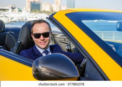 Successful yang businessman in yellow cabrio car.