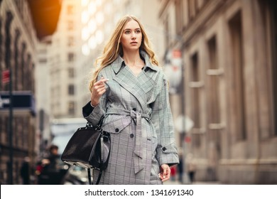 Successful young adult business woman with black bag walking to the job on New York City street at financial district