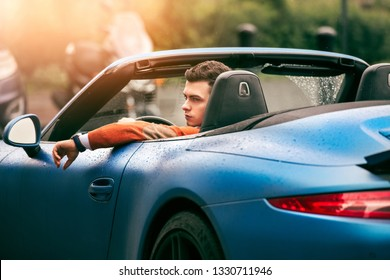 Successful young adult handsome man drives luxury convertible sport car at sunny day