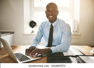 Successful young African businessman sitting at his desk in an office smiling and working on a laptop