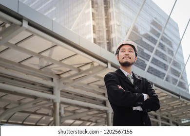 Successful young asian engineer man standing over modern building background