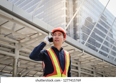 Successful young asian engineer man in uniform talking on phone over modern building background