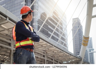 Successful young asian engineer man in uniform standing over modern building background and looking forward