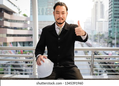 Successful young asian engineer man showing thumb up and standing over modern building background