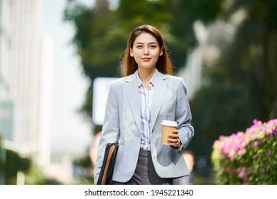 successful young asian female corporate executive walking on street holding a cup of coffee looking at camera