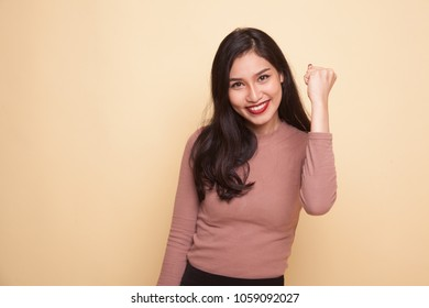 Successful  young Asian woman hold fist up on beige background