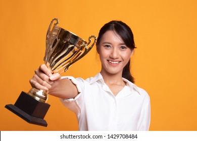 Successful young asian woman holding a trophy on yellow background
