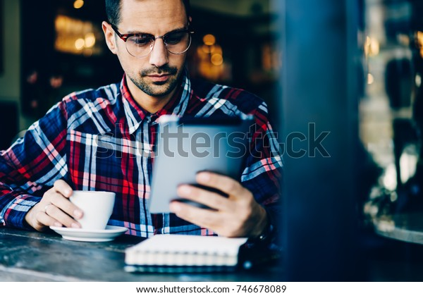 Successful young bearded man in eyewear reading news on websites via high speed 4G internet connected to digital tablet while sitting indoors in coffee shop and enjoying tasty drink in free time