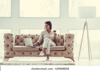 Successful young beautiful woman sitting on a sofa in the living room. using laptop and drinking red wine.