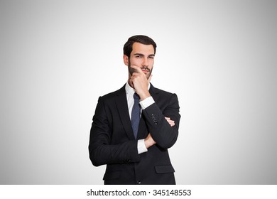 Successful young business man thinking and looking at the camera with confidence and seriousness, on gray background.