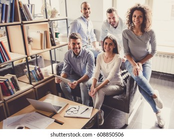 Successful young business people are looking at camera and smiling while working in office