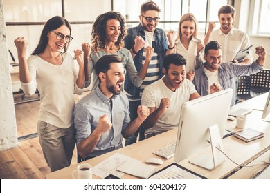 Successful young business people are raising hands in fists and screaming with happiness while working with a computer in business center