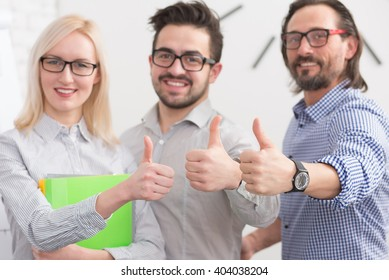 Successful young business people showing thumbs up signs. Business people in glasses smiling for camera.