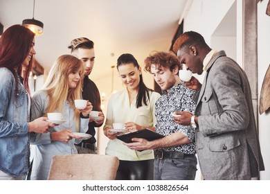 Successful young business people are talking and smiling during the coffee break in office.