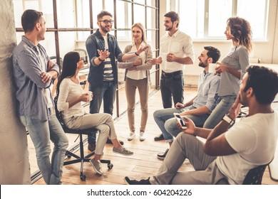 Les jeunes gens d'affaires prospères parlent et sourient pendant la pause café au bureau
