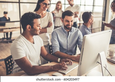 Successful young business people are using a computer and smiling while working in business center