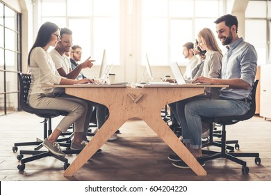 Successful young business people are using laptops, talking and smiling while working in business center