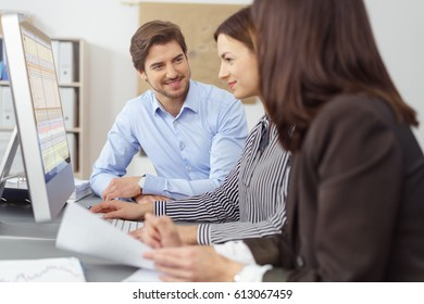 Successful young business team in a meeting sitting grouped around a desktop monitor with focus to a smiling woman typing on the computer