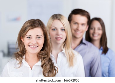 Successful young business team standing in an oblique row smiling at the camera with focus to a beautiful woman in the front with leadership qualities