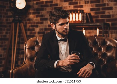 Successful young businessman in black suit with perfect hairstyle drinking cognac