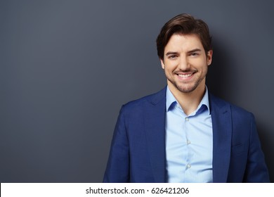 Successful young businessman in a blue suit with a lovely genuine smile posing against a dark grey background with copy space