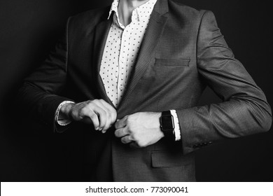 A successful young businessman in a business suit fastens a button and a white shirt and a fashionable watch on his hand against a black background. Stylish man. Male professions. Hands close up