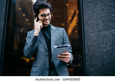 Successful young businessman dressed in formal suit happy with advantageous business offer received on mail on digital tablet standing outdoors near office building and talking on smartphone device