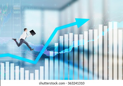 Successful young businessman with a folder in hand running up along a blue rising graph. Blurred office background. Concept of career growth.