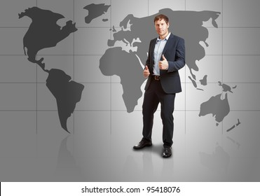 Successful young businessman in front of world map with thumbs up - success or achievement concept