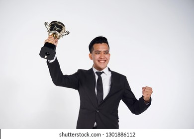 Successful young businessman holding a champion cup isolated on white