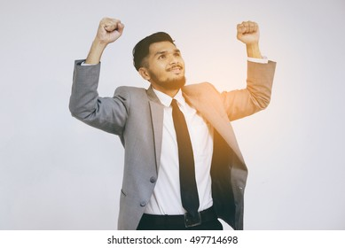Successful young businessman keeping arms raised celebrating his victory on grey background