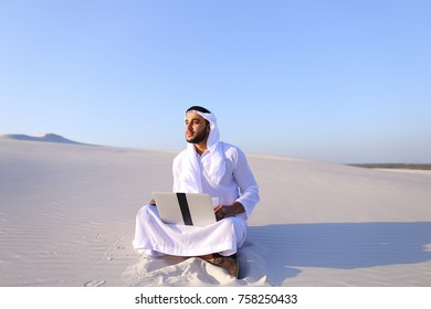 Successful young businessman male Muslim uses laptop to build drawing in Photoshop and prints fingers on laptop sitting on white sand in bottomless wide desert in afternoon against blue sky. Swarthy