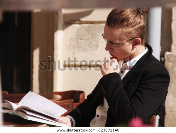 Successful young businessman reading a book in his spare time (freelance, time management, freedom concept)