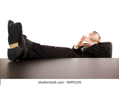 Successful young businessman relaxing over desk, isolated in white background