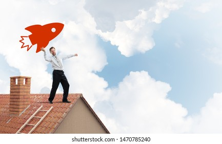 Successful and young businessman standing on the top of brick roof and throwing huge red rocket in the air with cloudy skyscape view on background.