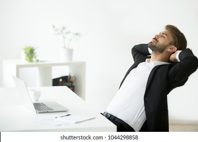 Successful young businessman in suit relaxing at workplace with laptop finished work, relaxed calm employee feels happy breathing fresh air, smiling ceo enjoys break in office, no stress free relief