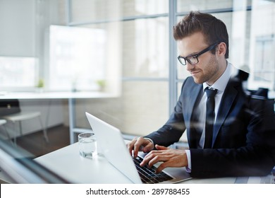 Successful young businessman typing on laptop at workplace