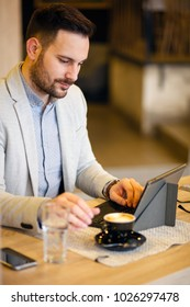 Successful young businessman using a tablet while working in a modern coffee shop. Work anywhere concept.