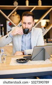 Successful young businessman using a tablet and drinking a cup of coffee while working in a modern coffee shop. Work anywhere concept.